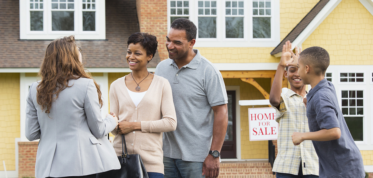 African-American family with agent in front of home