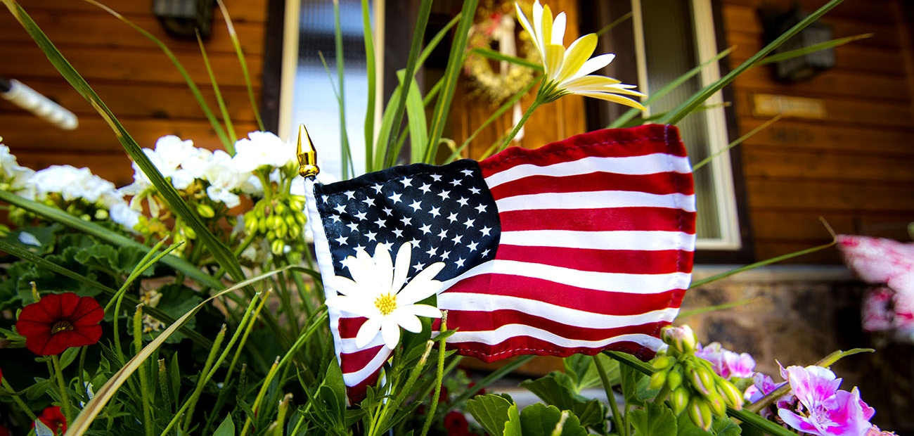 American flag in home flower bed