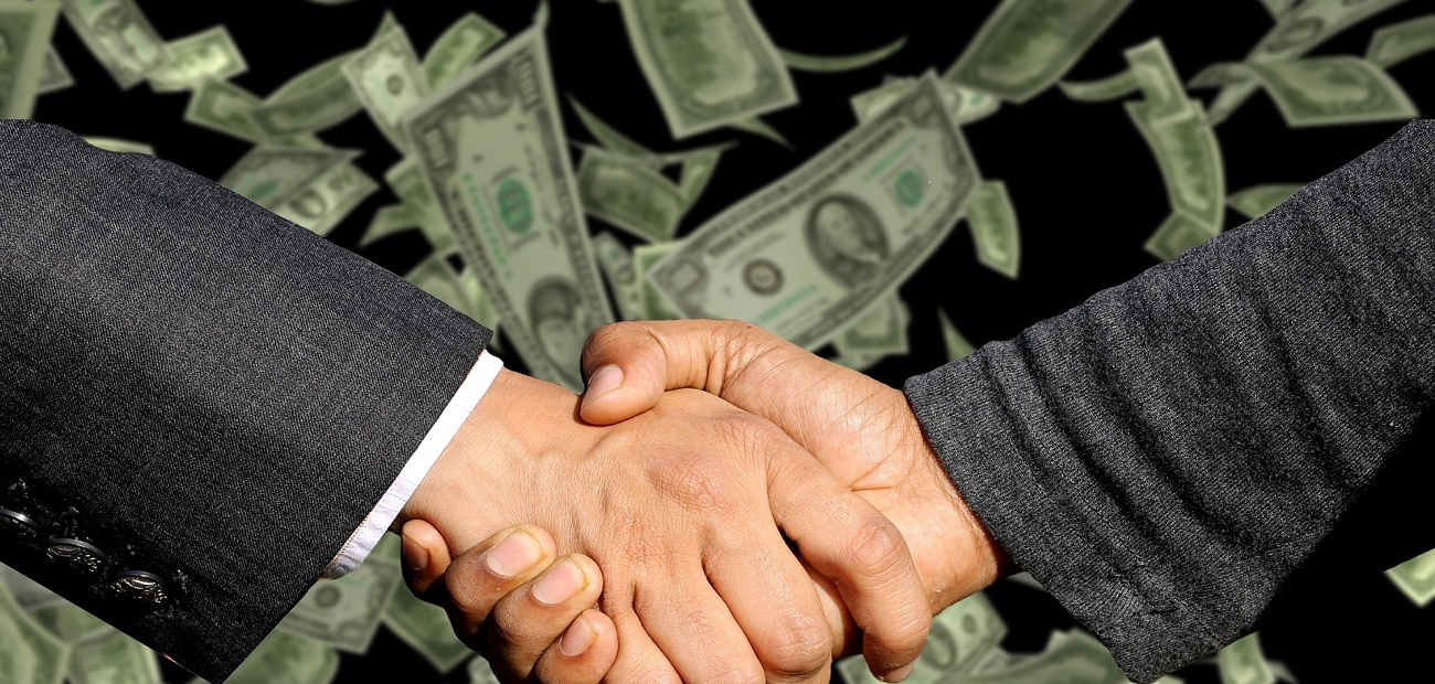 businessmen shaking hands with money in the background