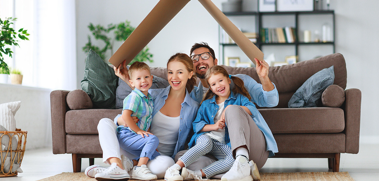 Family in a living room holding a cardboard roof