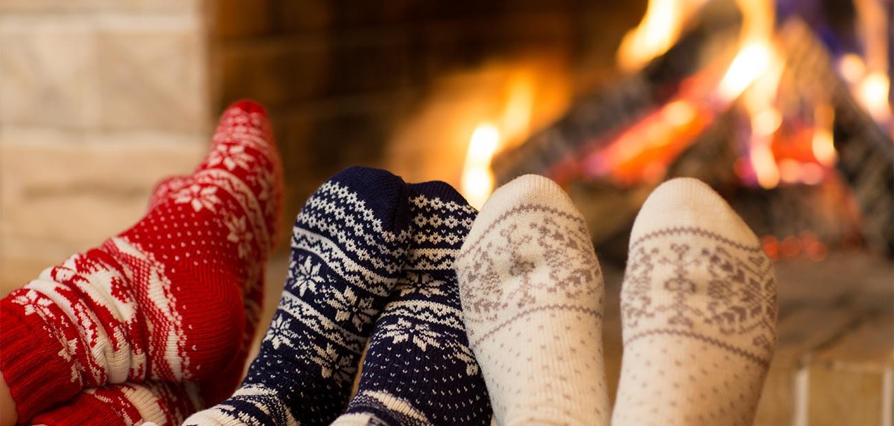 Feet in socks by the fireplace
