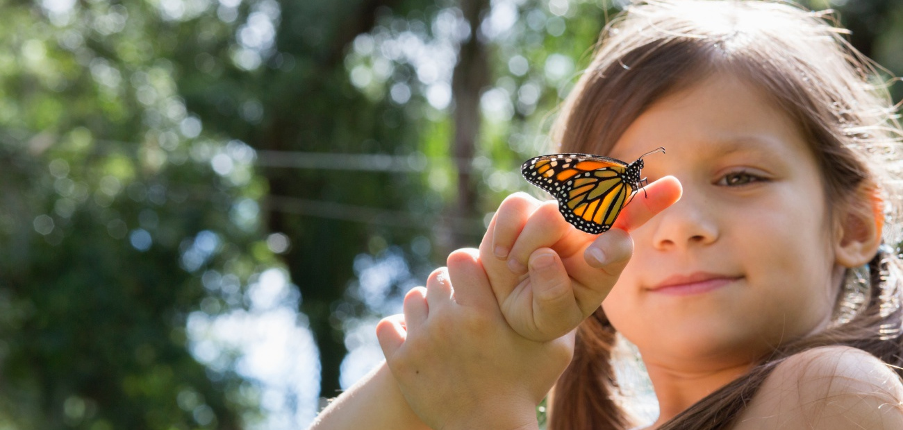 Girl holding monarch butterfly on finger