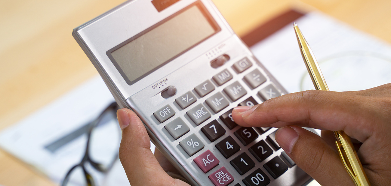 Hands holding calculator and pen