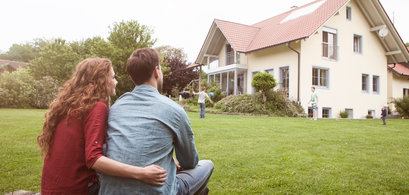 homeowners looking at home from lawn