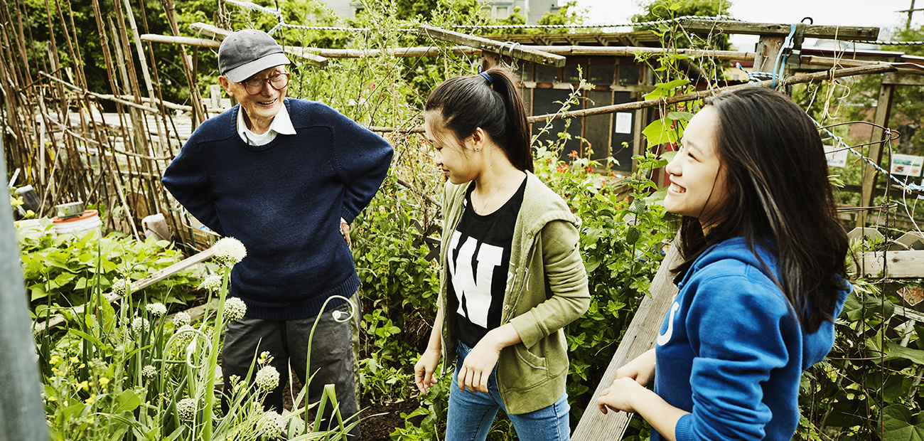 Older man with two young women in community garden