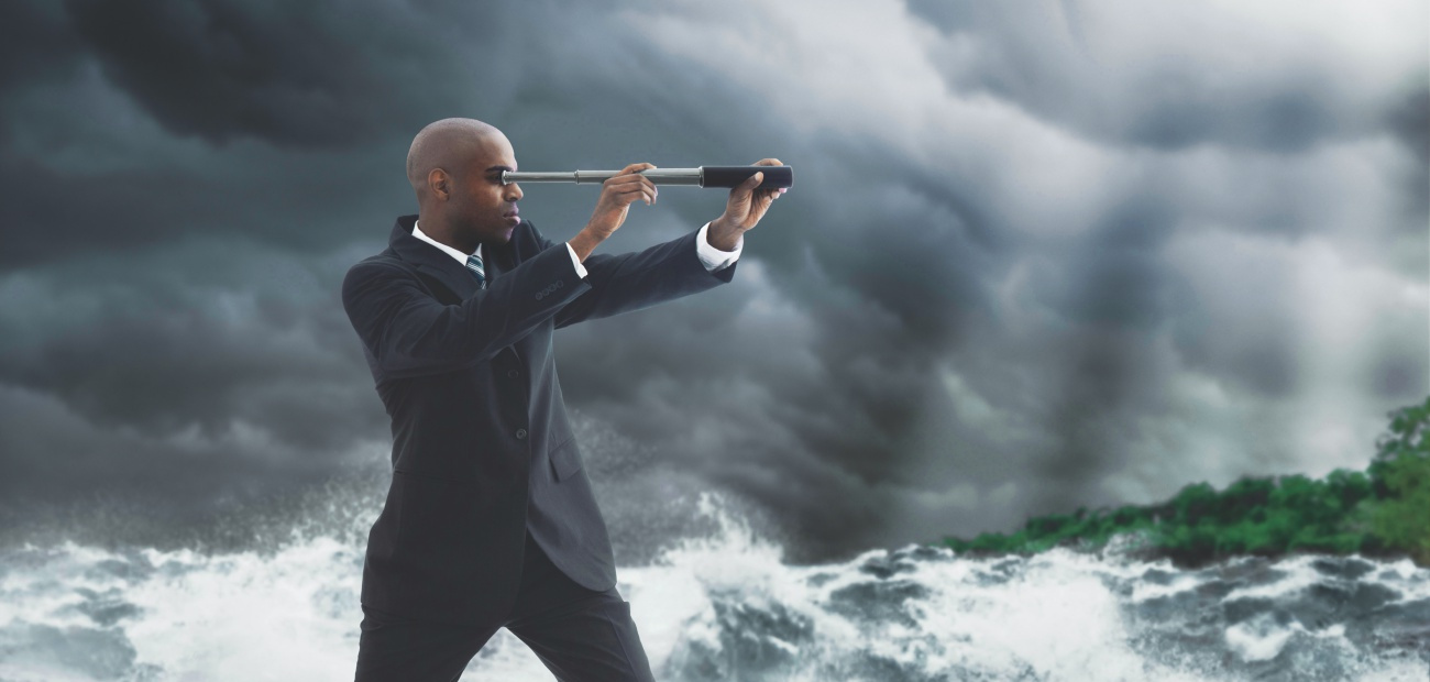Businessman standing on a boat with a telescope in choppy waters at sea