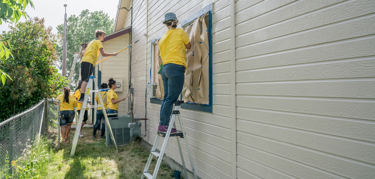 Volunteers painting a house