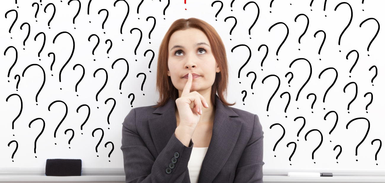 A Woman in business attire, looking thoughtful in front of a white board of question marks