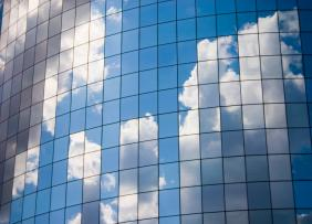 A bright blue sky and fluffy white clouds reflected in the curve of a skyscraper.
