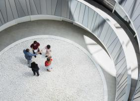View from above business people handshaking in round modern office atrium courtyard