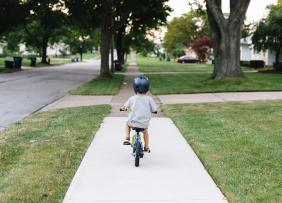 Child riding a bike in a suburban neighborhood