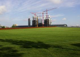 A large construction site near a large, grass field.