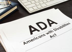 Americans with Disabilities Act ADA paperwork with keyboard, glasses and book