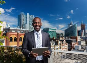 Outdoor portrait of African American businessman with digital tablet