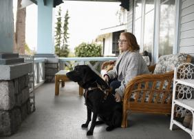 Visually impaired woman sitting with seeing eye dog on porch