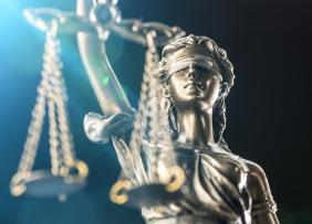 Close-Up Of Lady Justice Statue Against Black Background