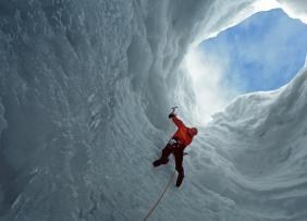 Mountaineer climbing out of ice and snow mountain