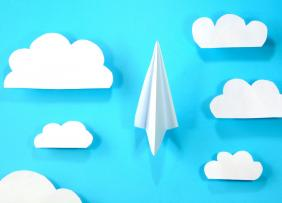 White paper plane flying between clouds.
