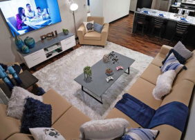 A Staged dorm living room with couches, TV, coffee table, white rug, and kitchen in the background