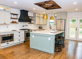 Mixed metal fixtures shown in an open kitchen with light blue island
