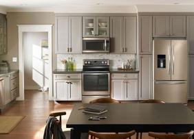 Sun lit kitchen with stainless steel bronze appliances counter and table