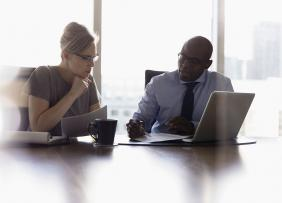 Woman and Man Consulting in Front of Bright Window