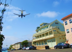 airplane overhead some small buildings