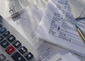 Calculator, receipts, tax forms, and a pen