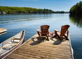 Canoe next to dock with two Adirondack chairs
