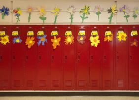 Red lockers in a school hallway, decorated with paper flowers