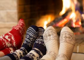 Feet in socks by the fireplace