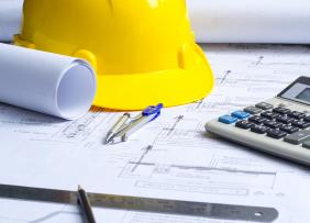 Hard hat, blueprints, and calculator