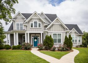 Large gray house with blue door and big lawn