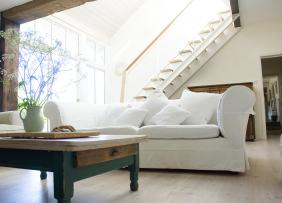 Living room with white couch and flowers, with a staircase and exposed wood beams