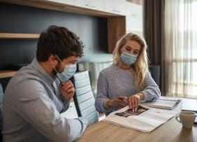 Man and woman wearing masks in office, going over papers