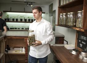 Man behind the counter of a marijuana dispensary