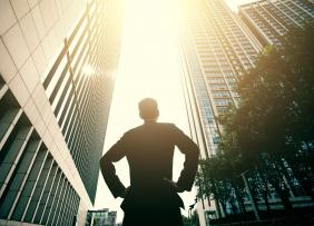Man in a suit looking up at tall buildings