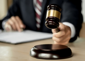 Man in a suit and tie holding a gavel