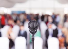 Microphone in front of blurred conference audience