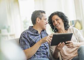 Middle-aged couple sitting on a couch with a tablet