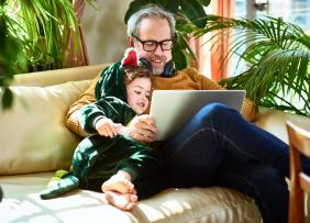 Middle-aged man and a child sitting on a couch and looking at a laptop