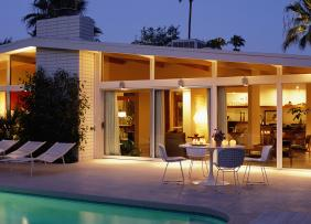 Modern house exterior at dusk, with patio and pool