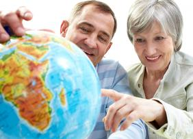 Older man and woman looking at a globe