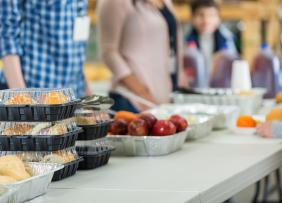 People standing next to a table of donated food
