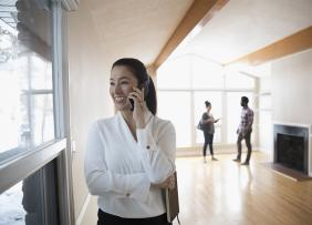 Real estate agent talking on the phone with clients exploring house in background
