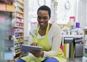 Small business owner in shop with tablet