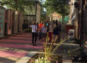 A pedestrian alley in Fitchburg, MA with boxes for artwork to go in, tables, chairs and very bright pink stripes on the walkway.