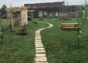 A park with a walking path, picnic tables, recently planted trees, and trellises.
