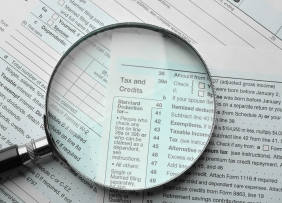 Tax forms with magnifying glass on tax and credits section