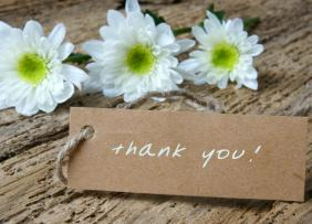 Thank you note on wood background with flowers